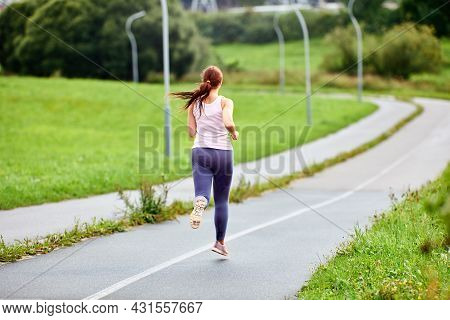 Back View Of Running Woman On Road At Summer Morning.