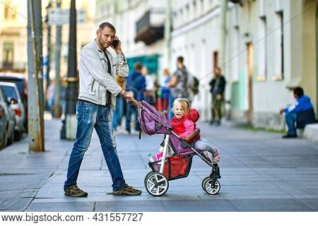 Man Talks By Smartphone While Walks With Little Girl In Baby Carriage.