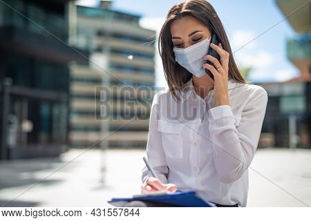 Masked young woman talking on the phone while writing notes, covid and coronavirus concept