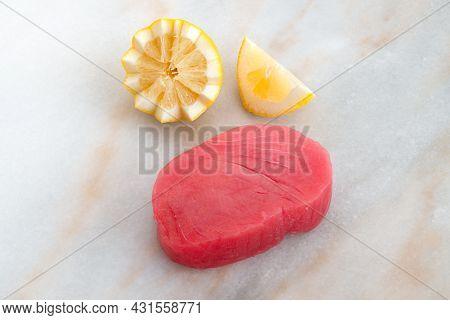 Fresh Cut Tuna Steak With Lemon Wedges On The Kitchen Counter