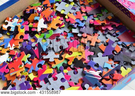 Closeup Heap Of Colorful Jigsaw Puzzle Game In A Box