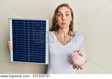 Young blonde woman holding photovoltaic solar panel and piggy bank puffing cheeks with funny face. mouth inflated with air, catching air.