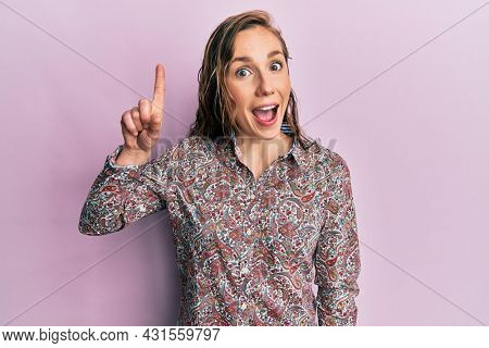 Young blonde woman wearing casual clothes smiling with an idea or question pointing finger up with happy face, number one