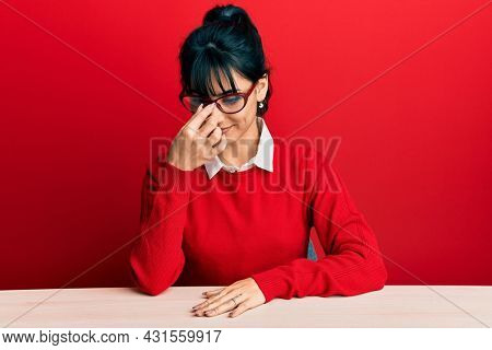Young brunette woman with bangs wearing glasses sitting on the table tired rubbing nose and eyes feeling fatigue and headache. stress and frustration concept.