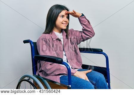 Young brunette woman sitting on wheelchair very happy and smiling looking far away with hand over head. searching concept.