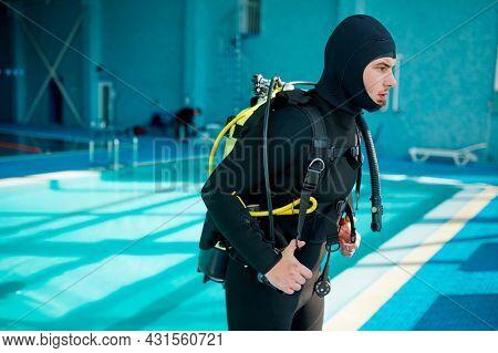 Male diver in scuba suit prepares for dive, diving