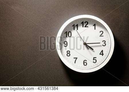 Modern White Wall Clock With Black Time Pointer Off Center On Black Background. Shadows On The Clock