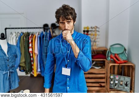 Young hispanic man working as manager at retail boutique feeling unwell and coughing as symptom for cold or bronchitis. health care concept.