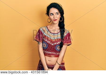 Young woman wearing bindi and bollywood clothing smiling looking to the side and staring away thinking.
