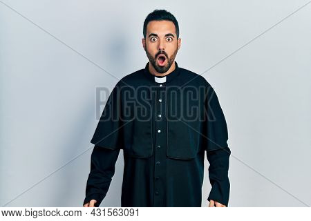 Handsome hispanic man with beard wearing catholic priest robe afraid and shocked with surprise and amazed expression, fear and excited face.