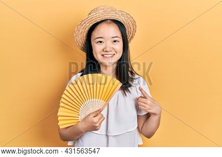 Young chinese girl waving hand fan cooling air in summer smiling happy pointing with hand and finger