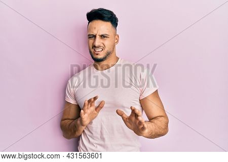 Young arab man wearing casual clothes disgusted expression, displeased and fearful doing disgust face because aversion reaction. with hands raised