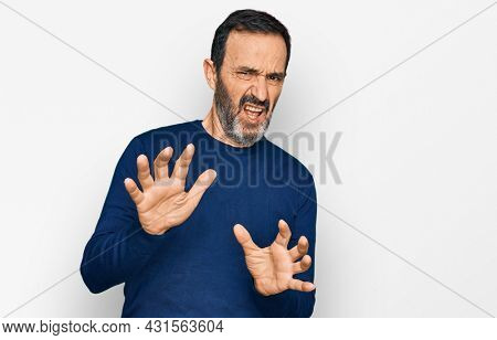 Middle age hispanic man wearing casual clothes disgusted expression, displeased and fearful doing disgust face because aversion reaction. with hands raised