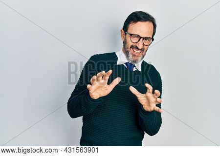 Middle age hispanic man wearing casual clothes and glasses disgusted expression, displeased and fearful doing disgust face because aversion reaction. with hands raised