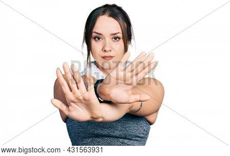 Young hispanic girl wearing sportswear and towel rejection expression crossing arms doing negative sign, angry face