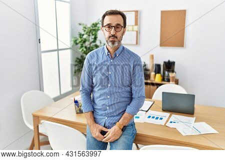 Middle age hispanic man with beard wearing business clothes at the office puffing cheeks with funny face. mouth inflated with air, crazy expression.
