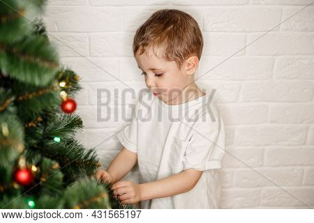 Child On Xmas Eve. Winter Holidays. Helping Mum With The Tree. Family Decorating Christmas Tree With