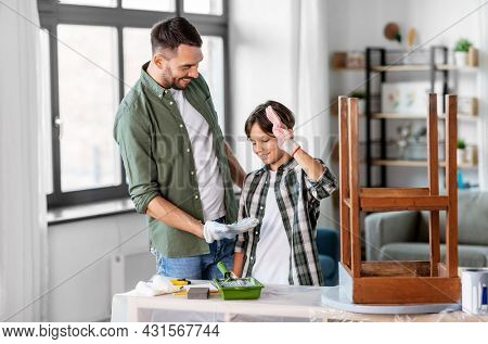 family, diy and home improvement concept - happy smiling father and son restoring old table and making low five gesture