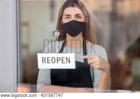 small business, reopening and service concept - woman in black mask with reopen banner on window or door glass