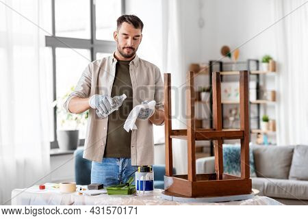 furniture restoration, diy and home improvement concept - man applying solvent to rag and renovating old wooden table
