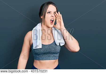 Young hispanic girl wearing sportswear and towel shouting and screaming loud to side with hand on mouth. communication concept.