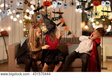 halloween, holiday and childhood concept - smiling boy and girls in costumes playing and scaring each other at home at night