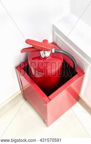 Hand-held Fire Extinguisher Stands In The Corner Of The Office. Red Fire Extinguisher In Box Against