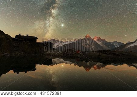 Incredible night view of Lac Blanc lake in France Alps. Monte Bianco mountain range on background. Vallon de Berard Nature Preserve, Chamonix, Graian Alps. Landscape astrophotography
