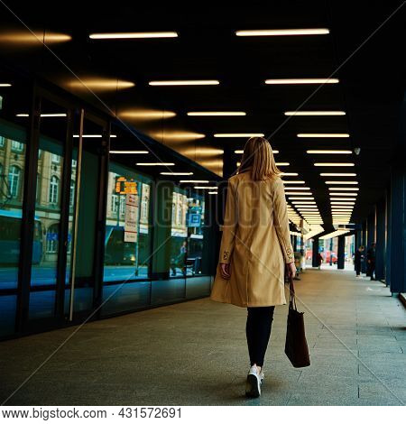 Stylish Millenial Woman In Coat Walks At City Street With Bag, Back View