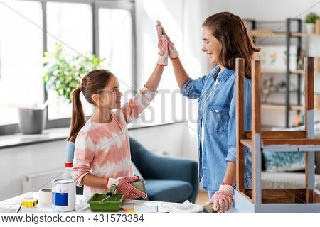 furniture renovation, diy and home improvement concept - happy smiling mother and daughter with sanding sponge and old wooden table making high five gesture at home