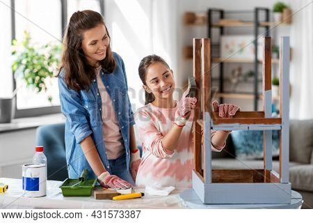 furniture renovation, diy and home improvement concept - happy smiling mother and daughter sanding old round wooden table with sponge at home