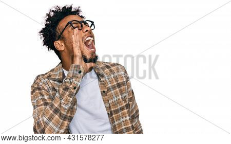 Young african american man with beard wearing casual clothes and glasses shouting and screaming loud to side with hand on mouth. communication concept.