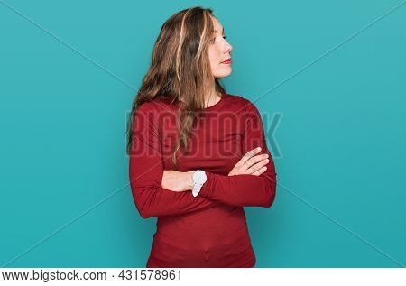 Young blonde woman wearing casual clothes looking to the side with arms crossed convinced and confident
