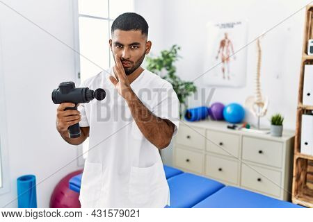 Young indian physiotherapist holding therapy massage gun at wellness center hand on mouth telling secret rumor, whispering malicious talk conversation