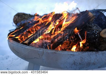 Firewood In The Winter Snow Garden.burning Firewood Background.flames And Sparks