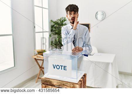 Hispanic man with beard voting putting envelop in ballot box hand on mouth telling secret rumor, whispering malicious talk conversation