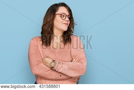 Young plus size woman wearing casual clothes and glasses looking to the side with arms crossed convinced and confident