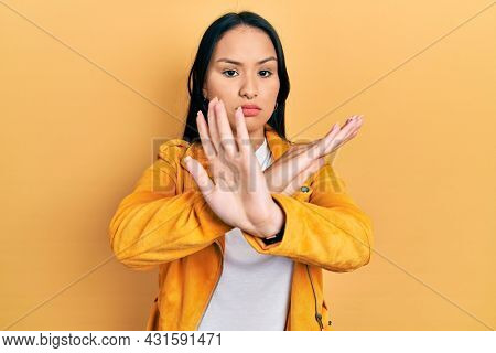 Beautiful hispanic woman with nose piercing wearing yellow leather jacket rejection expression crossing arms doing negative sign, angry face