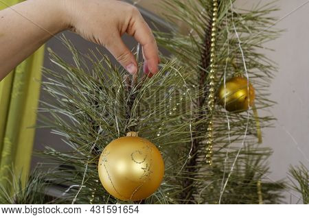 Woman Decorating A Christmas Tree. Adult Woman Hangs Festive Balls, Garlands, Tinsel On The Branches