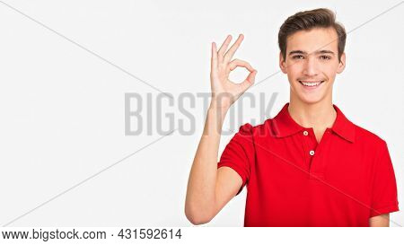 Portrait of happy young man showing okay gesture, isolated over white background. Photo of smiling  Handsome white guy in a red shirt with sign OK. Positive Male person shows gesture OKAY .