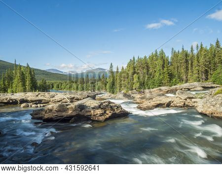 Beautiful Landscape With Long Exposure Water Stream And Cascade Of River Kamajokk, Boulders And Spru