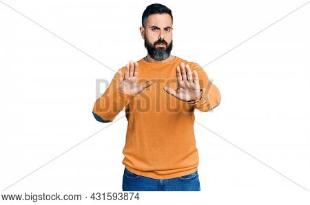 Hispanic man with beard wearing casual winter sweater moving away hands palms showing refusal and denial with afraid and disgusting expression. stop and forbidden.