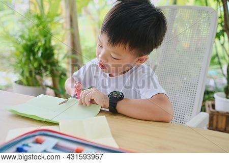 Cute Asian Kindergarten Boy Cutting A Piece Of Paper, Introduce Scissor Skills For Toddlers, Little