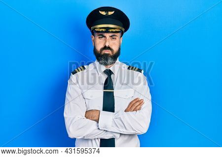 Young hispanic man wearing airplane pilot uniform with arms crossed gesture puffing cheeks with funny face. mouth inflated with air, catching air.