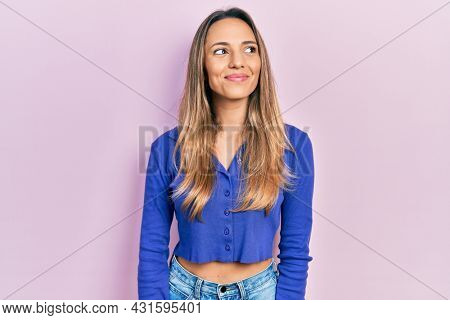 Beautiful hispanic woman wearing casual blue shirt smiling looking to the side and staring away thinking.