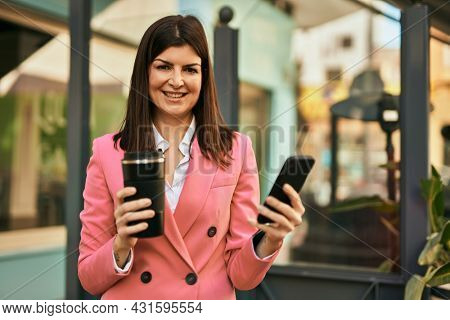 Middle age business woman using smartphone outdoors, typing a message