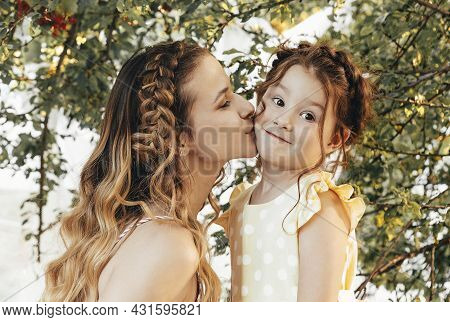 Maternity And Loving Motherhood. Beautiful Young Mom With Braided Hair Kissing Her Lovely Little Swe