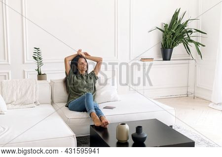 Harmony And Balance Concept. Carefree And Serene Indian Woman Resting On The Comfortable Couch At Ho
