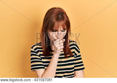 Redhead young woman wearing casual striped t shirt feeling unwell and coughing as symptom for cold or bronchitis. health care concept.