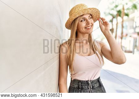 Beautiful blonde woman smiling happy outdoors on a sunny day wearing summer hat leaning on the wall